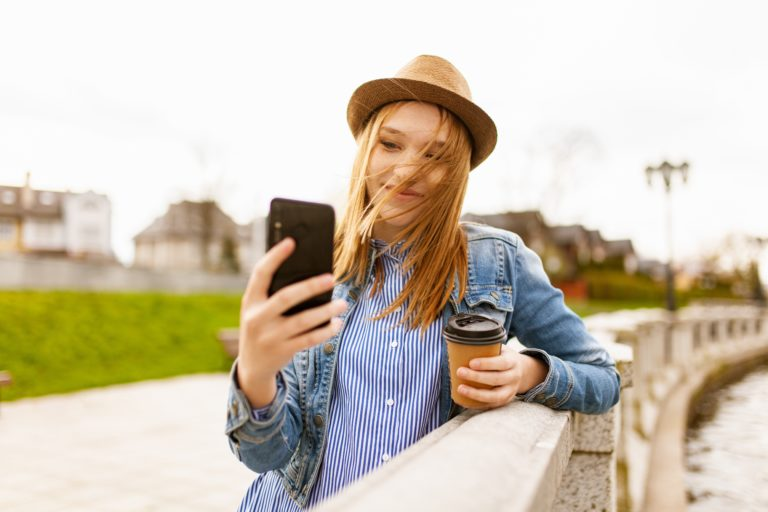 young lady checking phone with coffee