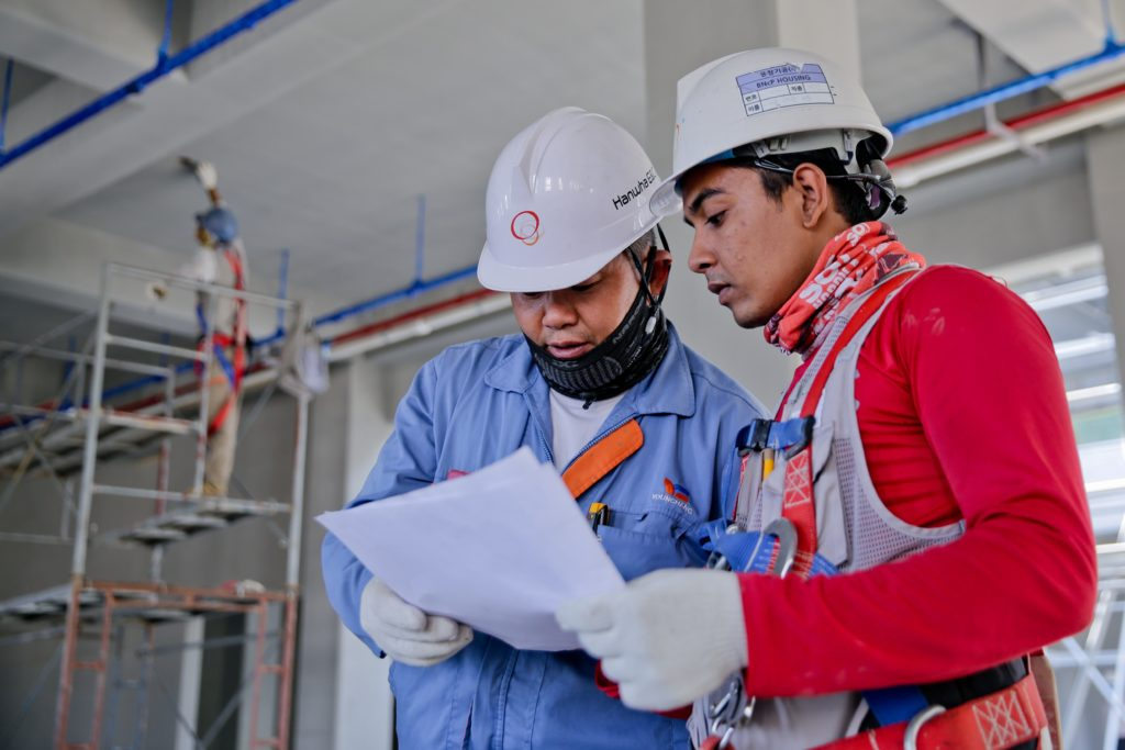 two construction workers reading a paper